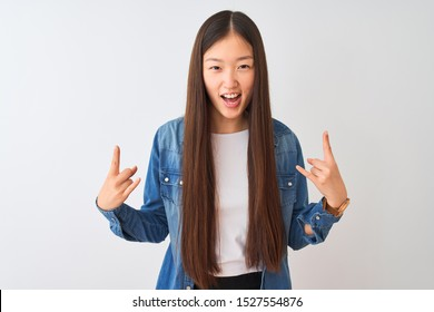 Young chinese woman wearing denim shirt standing over isolated white background shouting with crazy expression doing rock symbol with hands up. Music star. Heavy concept.