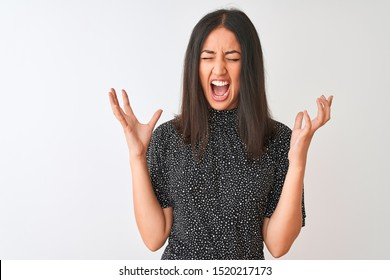 Young chinese woman wearing elegant t-shirt standing over isolated white background celebrating mad and crazy for success with arms raised and closed eyes screaming excited. Winner concept