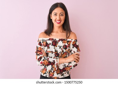 Young chinese woman wearing floral t-shirt standing over isolated pink background happy face smiling with crossed arms looking at the camera. Positive person.