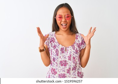 Young chinese woman wearing floral t-shirt and pink glasses over isolated white background celebrating mad and crazy for success with arms raised and closed eyes screaming excited. Winner concept