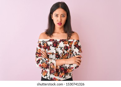 Young chinese woman wearing floral t-shirt standing over isolated pink background skeptic and nervous, disapproving expression on face with crossed arms. Negative person.