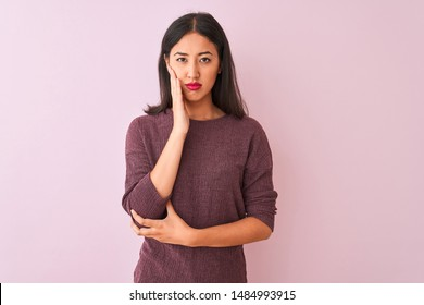 Young chinese woman wearing purple sweater standing over isolated pink background thinking looking tired and bored with depression problems with crossed arms.