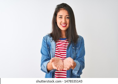 Young chinese woman wearing striped t-shirt and denim shirt over isolated white background Smiling with hands palms together receiving or giving gesture. Hold and protection