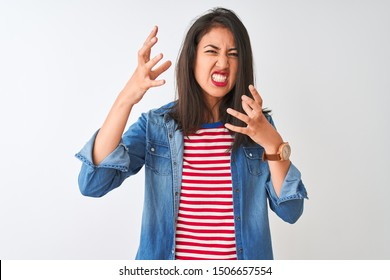 Young chinese woman wearing striped t-shirt and denim shirt over isolated white background Shouting frustrated with rage, hands trying to strangle, yelling mad
