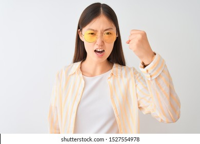 Young chinese woman wearing striped shirt and glasses over isolated white background annoyed and frustrated shouting with anger, crazy and yelling with raised hand, anger concept