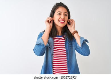 Young chinese woman wearing striped t-shirt and denim shirt over isolated white background Smiling pulling ears with fingers, funny gesture. Audition problem