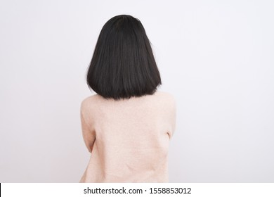 Young chinese woman wearing turtleneck sweater standing over isolated white background standing backwards looking away with crossed arms