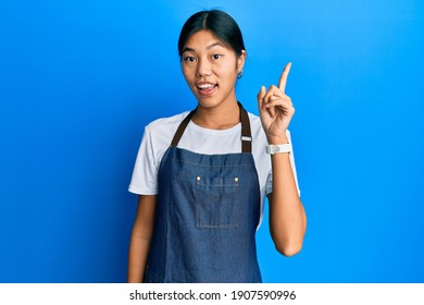Young chinese woman wearing waiter apron pointing finger up with successful idea. exited and happy. number one.