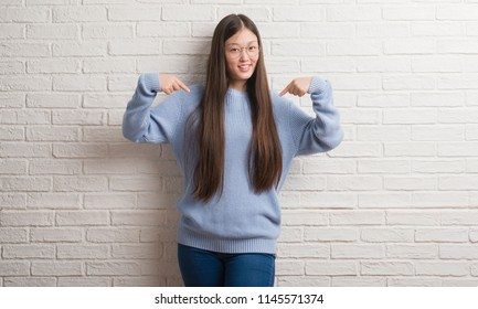 Young Chinise woman over white brick wall looking confident with smile on face, pointing oneself with fingers proud and happy.