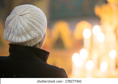 Young christian female looking at candle flames in church during praying