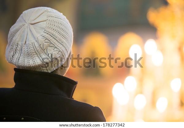 Jeune femme chrétienne regardant les flammes des bougies à l'église pendant la prière