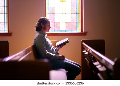 A young Christian man is sitting alone in a dark, empty church pew, by a bright stained glass window, worshiping God as he reads the Holy Bible.
