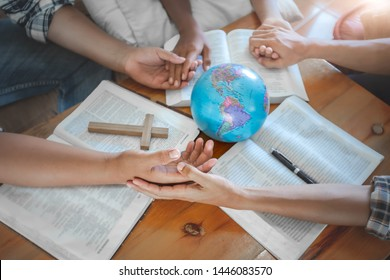 Young christian praying for globe and people around the world on wooden table with bible.
