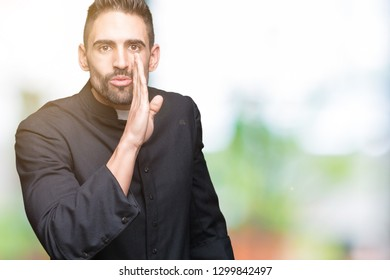 Young Christian priest over isolated background hand on mouth telling secret rumor, whispering malicious talk conversation
