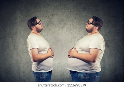 Young chubby man looking at fat himself feeling bloated. Diet and nutrition choice  healthy lifestyle concept
