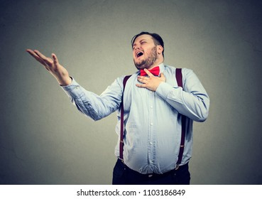 Young chubby man screaming in feelings of broken heart looking desperate while playing drama scene