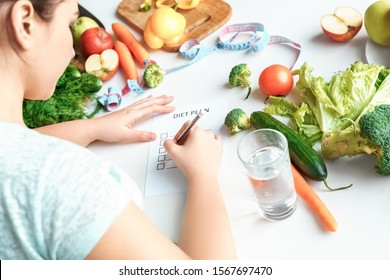 Young chubby woman sitting at table in kitchen with glass of water writing rules of diet plan concentrated back view close-up