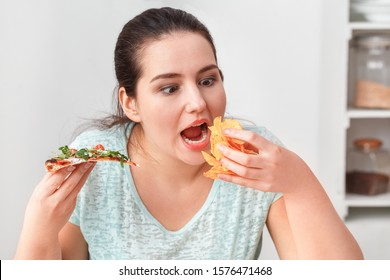 Young chubby woman sitting at table in kitchen binge eating eating slice of pizza and chips hungry close-up
