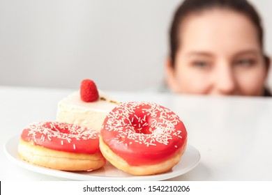 Young chubby woman standing in kitchen hiding under table looking at plate with doghnuts and cake close-up blurred background