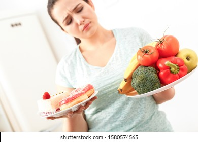 Young chubby woman standing in kitchen choosing bewtween plate with fresh fruits and vegetables and plate of desserts doubtful close-up blurred background