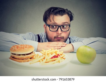 Young chunky man wanting tempting burger instead of healthy apple looking concerned.
