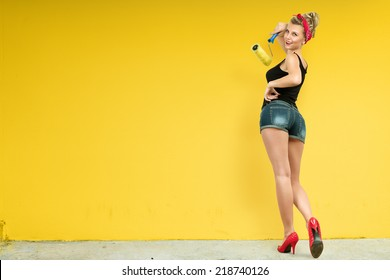 Young classic pin-up woman painting wall with paint roller