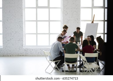 Young classmates writing testing quality control sitting at desk in modern loft interior office, male and female coworkers collaborating on creation startup discussing ideas with professional coach