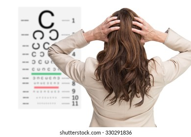 Young classy businesswoman with hands on head standing back to camera against eye test