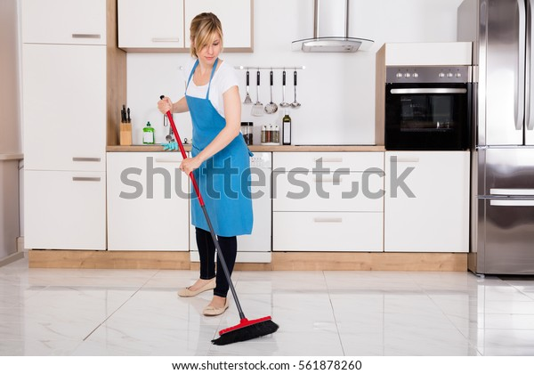 Young Cleaner Housemaid Sweeping Floor With Broom In Kitchen