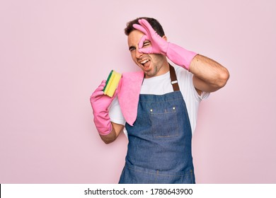 Young cleaner man with blue eyes cleaning wearing apron and gloves using clean scourer with happy face smiling doing ok sign with hand on eye looking through fingers