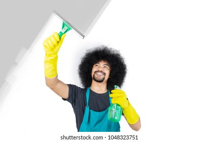 Young cleaning service professional cleaning the window isolated over white