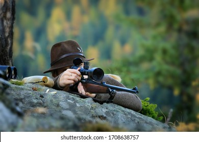 Young, Clever Woman Deer Hunter wearing green uniform with Rifle on the rock in Background autumn trees