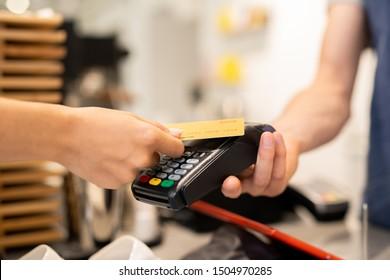 Joven cliente de café con una tarjeta de plástico sobre una máquina de pago electrónica en poder del camarero o del barista mientras paga por comida o bebida