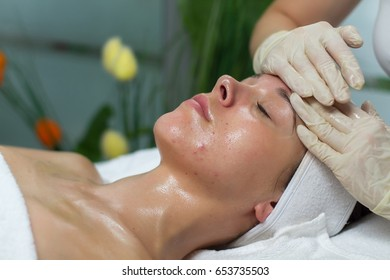 A young client is lying on her back on a table in a massage studio. She is having a facial massage and a beautician is gently massaging her forehead.