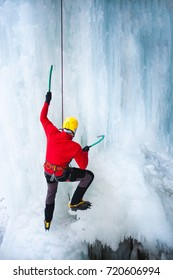 A young climber climbs on ice climbing and winter sport activities in cold weather.