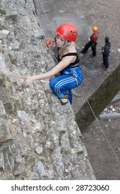 Young climber training on the old wall and answer by mobile