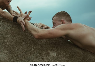 Young Climbers Rock Climbing. Adventure couple. Young romantic couple in love have fun on beautiful day. Hands concept. Help me. Strong man. Fitness concept. Sport photo. Love story concept. Sports