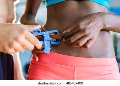 Young coach is measuring his body fat of sporty woman with calipers.