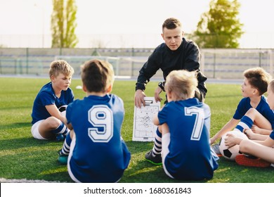 Young coach teaching kids on football field. Football coach coaching children. Soccer football training session for children. Football tactic education. Coach explains a game strategy using board