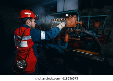 young coal miner is underground in mine for coal mining in overalls against. concept of repair of industrial equipment.