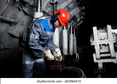 young coal miner is underground in a mine for coal mining in overalls against the backdrop of mining equipment.