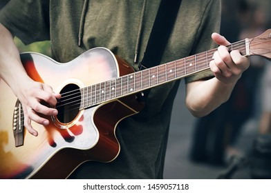 A young cocky guy in a green hoodie plays a bright colored acoustic six-string guitar, holding the chords with one hand and holding a mediator in the other. Man creates creativity and improvises.