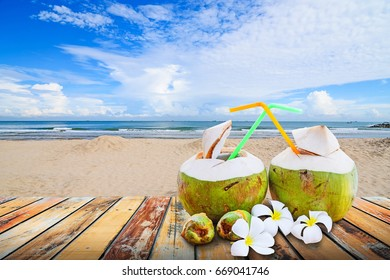 Young coconut juiced with plumeria flower on wood floor against blurred beach background. Summer holiday concept,
