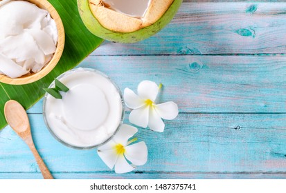 Young coconut pudding served in a glass cup decorated with coconut meat looks delicious on the banana leaves and a beautiful blue wooden table. Top view.