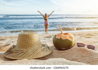A young coconut with a solvin hat and sunglasses lies on the beach on the sand. Summer background. Summer holiday concept