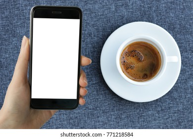 Young coffee addict woman using smart phone with white blank screen taking photo of hot espresso bombon in white ceramic coffee cup on blue tablecloth background. image for mock up.
