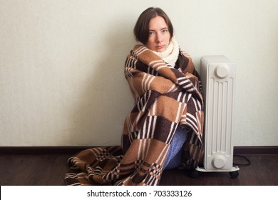 Young Cold Woman Wrapped In Blanket Sitting Near electric Heater At Home. Autumn or winter concept of domestic comfort, loneliness