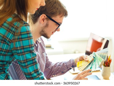 Young colleague - manand woman looking to a color paint palette at home office, modern business concept