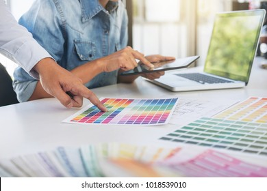 Young colleagues designers working together on a creative project and color samples for selection, Color swatch samples, Brainstorming Planning Partnership, creative graphic design working desktop.