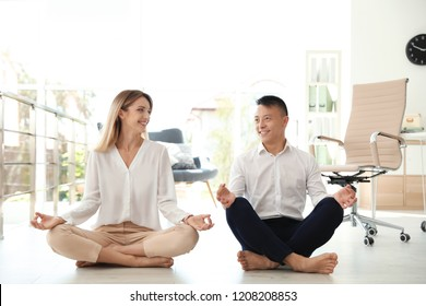 Young colleagues doing yoga in office. Workplace fitness